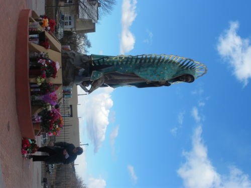 A Woman Restores Some Flowers At St. Guadlupe's Feet